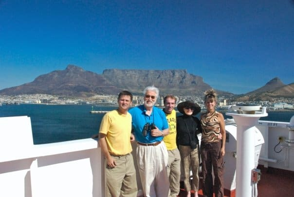 passengers on cargo freighter with cape town and table mountain in background