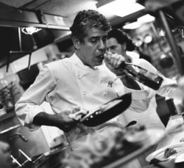 anthony bourdain cooking in kitchen in B&W