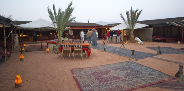 the tents, tables, cushions and more set up for a dinner feast