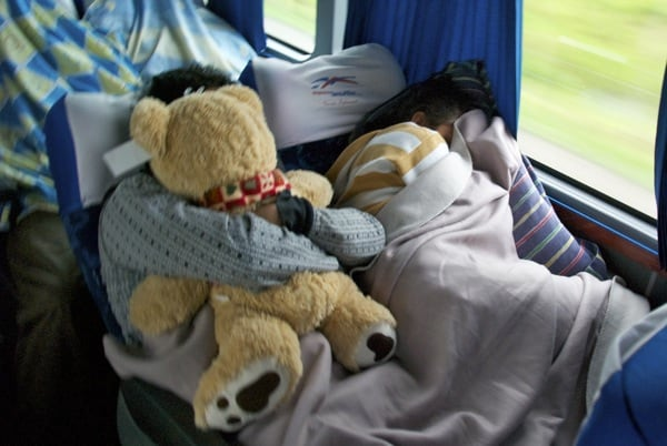guy traveling with teddy bear on bus