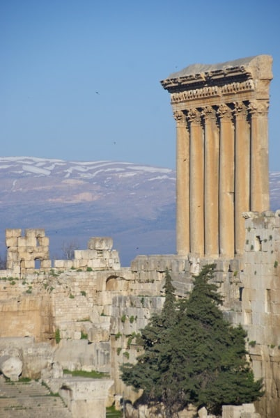 the remaining facade of the Temple of Jupiter, with snow capped mountains...