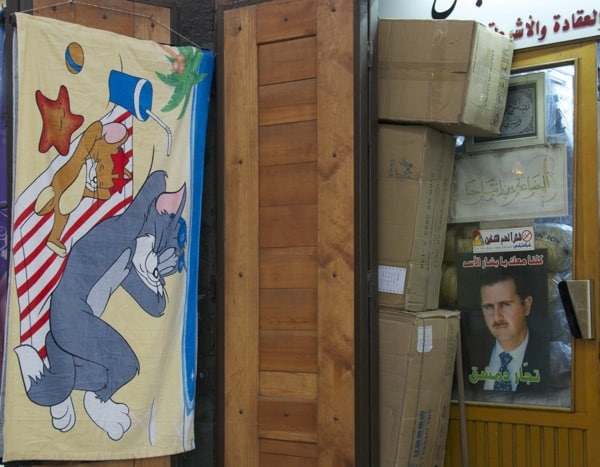 cartoon next to Assad poster syria