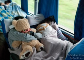 man sleeping with teddy bear on south american bus