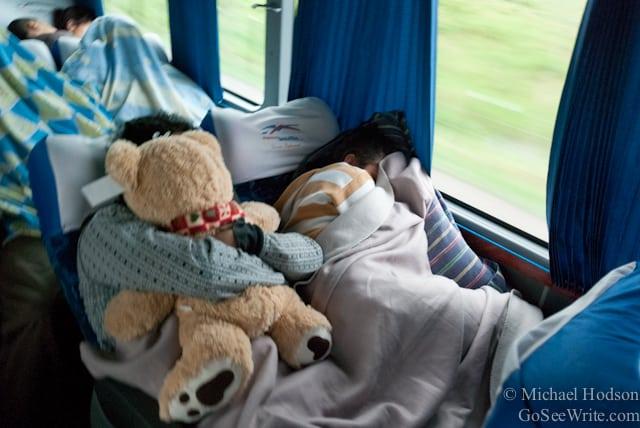 man sleeping with teddy bear on south american bus