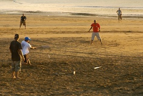 kids playing baseball on the beach