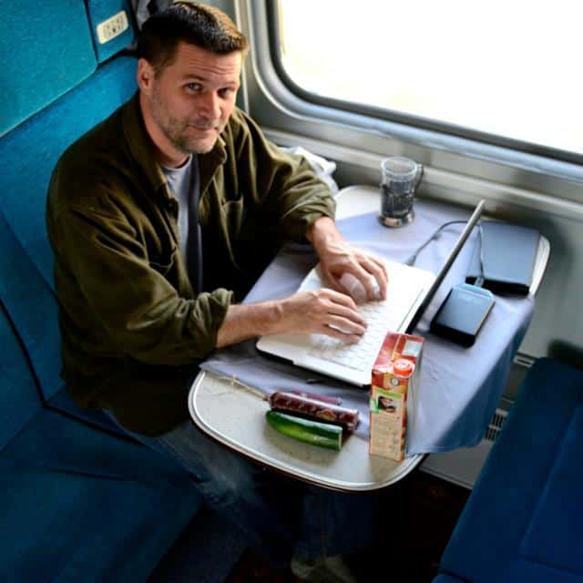 michael hodson writing on computer in train