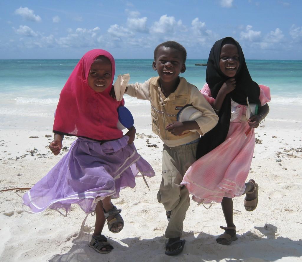 african kids playing on beach in zanzibar