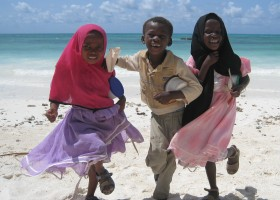 african kids playing on beach in zanzibar