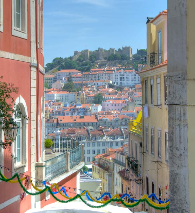 lisbon castle in distance through buildings