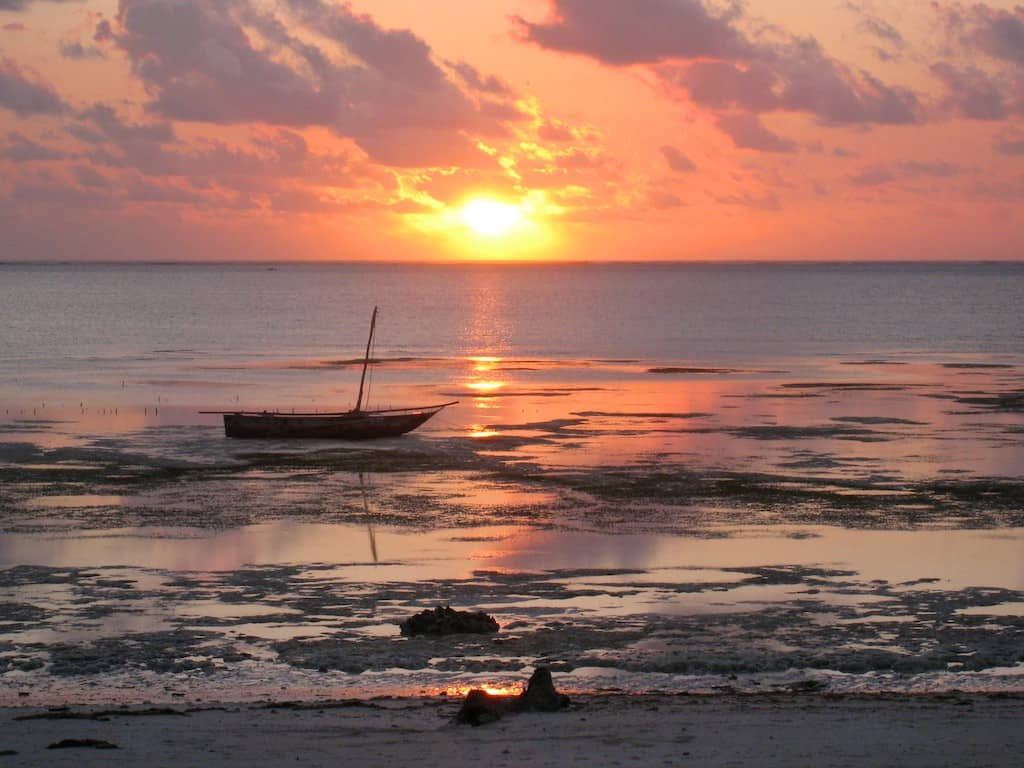 sunrise zanzibar with a beached boat