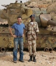 Somalia military bodyguard in front of tank, during overland africa travel