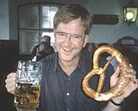 rick steves drinking a beer and eating a pretzel