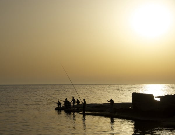 Byblos Lebanon Sunset over fishermen with long rods