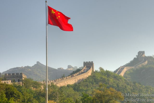 chinese flag flying over great wall of china
