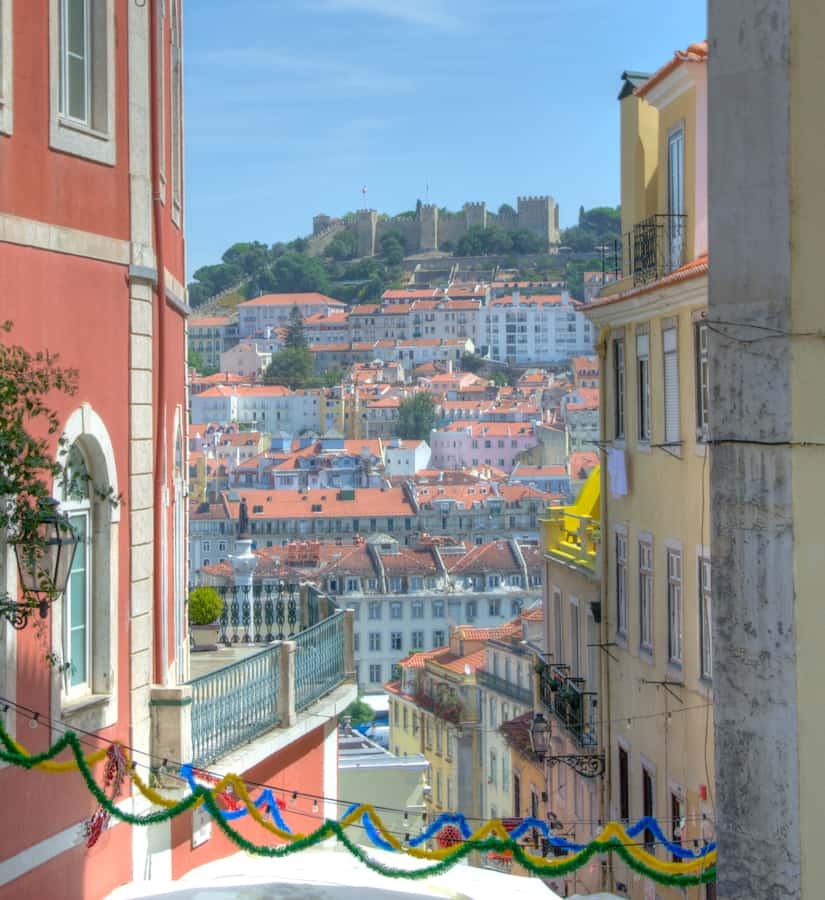 lisbon castle in distance through buildings